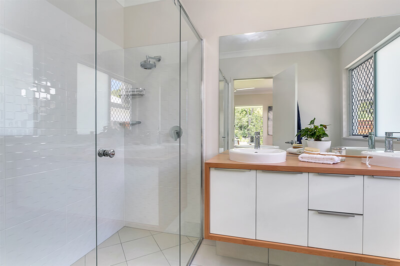 Timber and white vanity in modern bathroom with twin shower heads