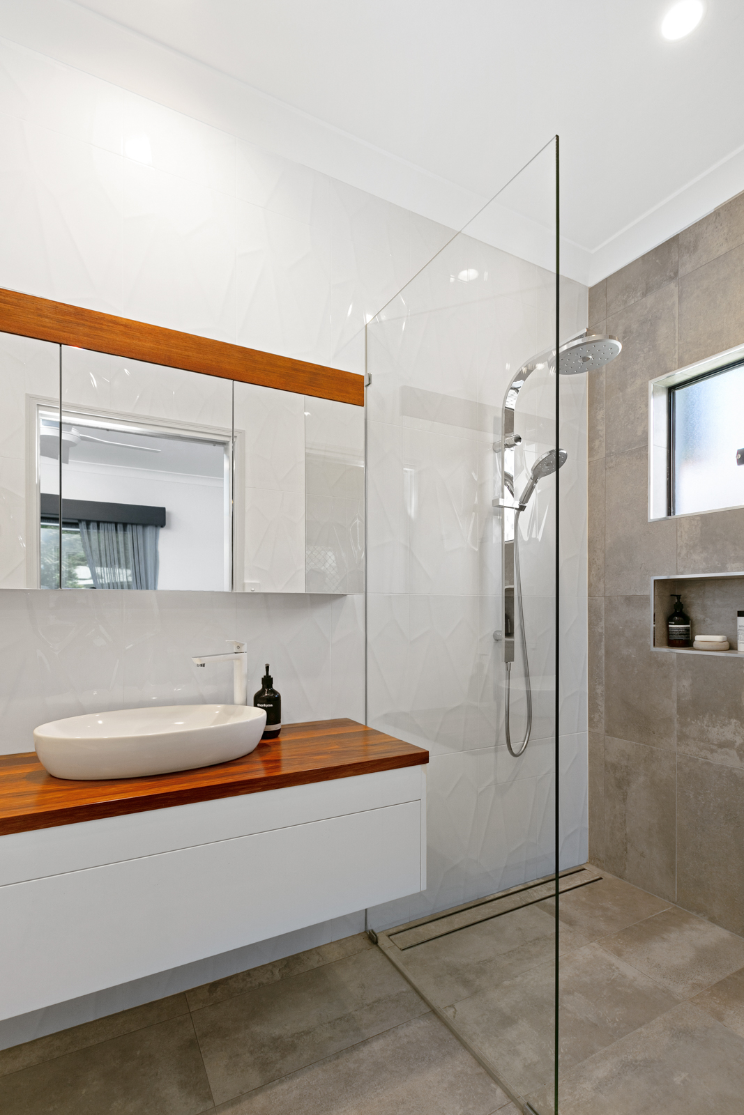 Renovated bathroom including wall-to-ceiling tiles, shower niche & timber floating vanity.