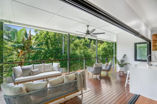 Bifold doors and windows join to make a wall disapear in tropical home.