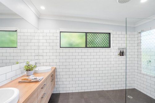 Esuite with subway tiles and timber vanity.