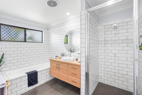 Main bathroom in custom designed home with subway tiles and sublime teak vanity.