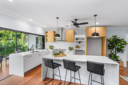 Kitchen with timber cabinets and bi-fold windows